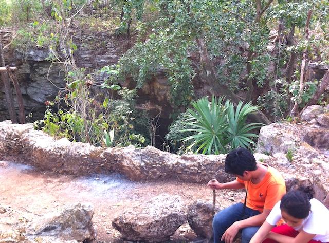 Niños descansan junto a un imponente cenote de una comisaría de Tixhualatún