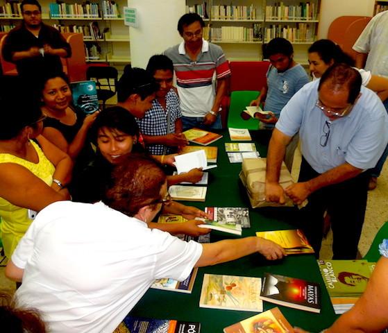 Estudiantes de literatura en lengua maya mirando los títulos donados por Sedeculta