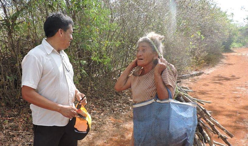 Una mujer que vuelve de leñar conversa con Bernardo Caamal Itzá, candidato maya a alcalde de Peto